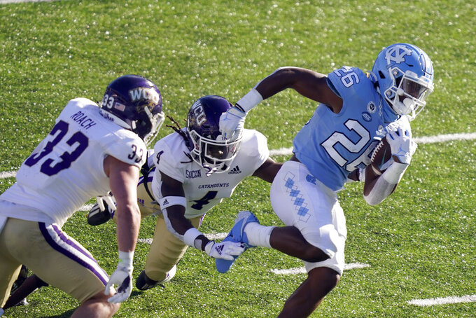 North Carolina running back D.J. Jones (26) runs the ball while Western Carolina linebacker Curtis Roach (33) and safety A.J. Rogers (4) during the second half of an NCAA college football game in Chapel Hill, N.C., Saturday, Dec. 5, 2020. (AP Photo/Gerry Broome)