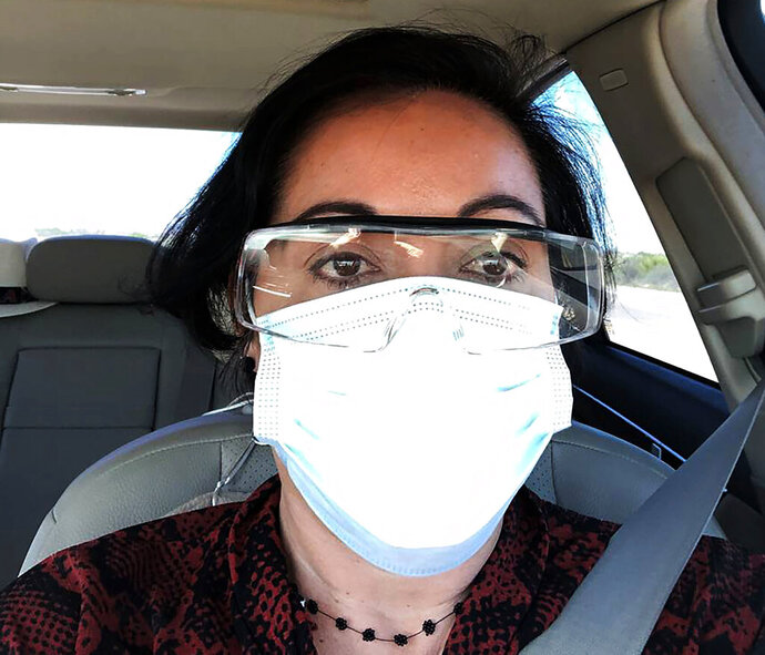 This March 23, 2020 photo provided by Margarita Silva shows her outside the La Palma Detention Center in Eloy, Ariz., wearing her husband's land surveyor goggles, a mask she borrowed from a friend and medical gloves she got from a hardware store. Attorneys and judges in U.S. immigration courts are trying to protect themselves from the coronavirus with borrowed masks and hand sanitizer. The Trump administration has delayed hearings for immigrants who aren't in detention but is moving forward for those who are. (Margarita Silva via AP)
