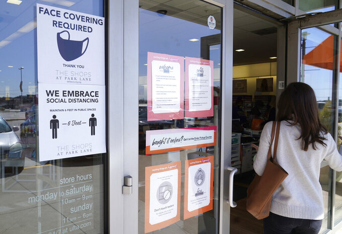 FILE - A customer enters a store with a face mask required sign displayed in Dallas, in this Tuesday, March 2, 2021, file photo. Although nearly a fifth of U.S. states don't require people to wear masks to protect against COVID-19, some businesses are requiring employees and customers to be masked on their premises. (AP Photo/LM Otero, File)