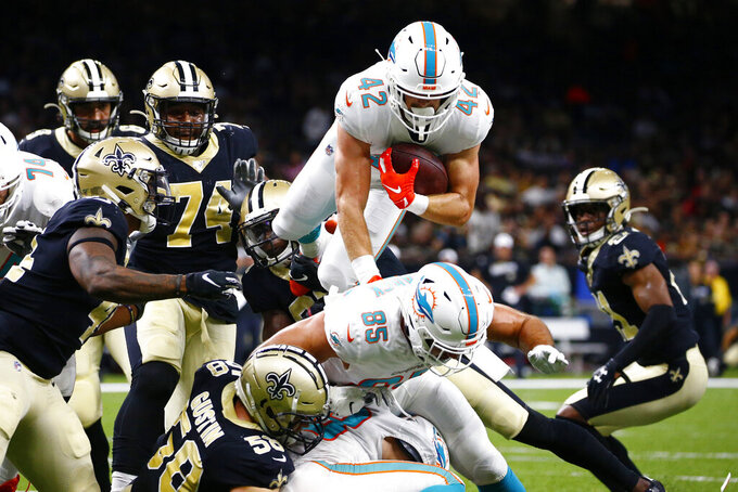 Miami Dolphins running back Patrick Laird (42) dives over the pile in the first half of an NFL preseason football game against the New Orleans Saints in New Orleans, Thursday, Aug. 29, 2019. (AP Photo/Butch Dill)