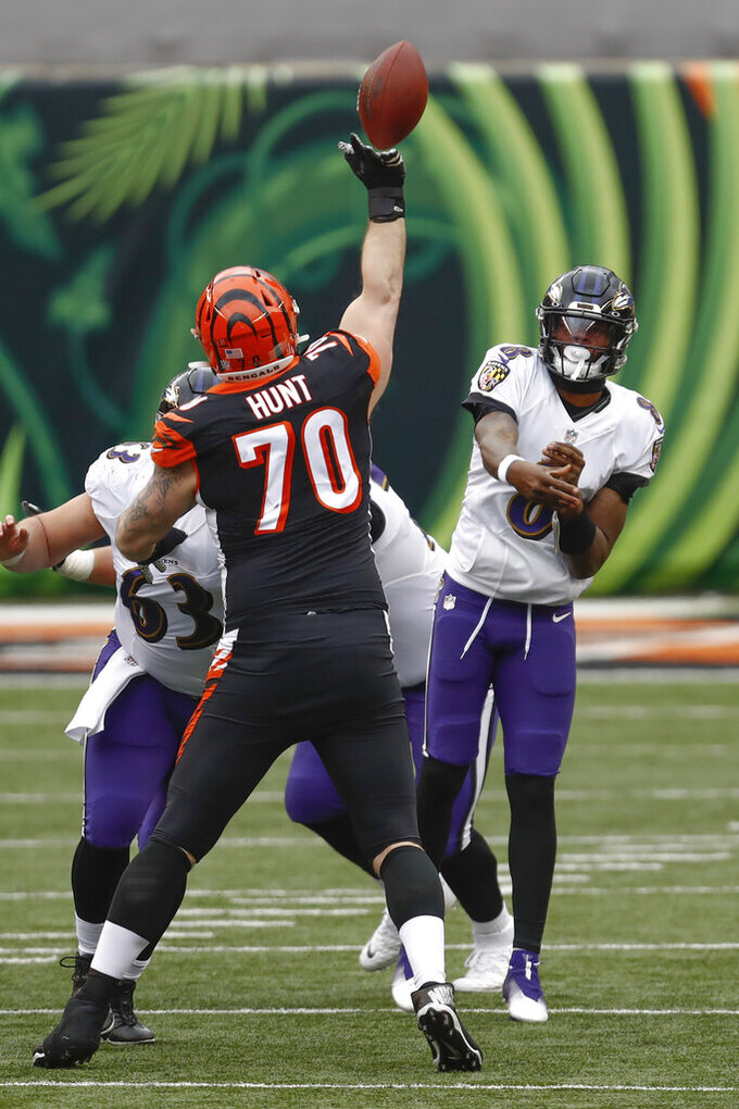 Cincinnati Bengals defensive end Margus Hunt (70) blocks a pass by Baltimore Ravens quarterback Lamar Jackson (8) that Ravens linebacker Akeem Davis-Gaither (59) intercepted during the first half of an NFL football game, Sunday, Jan. 3, 2021, in Cincinnati. (AP Photo/Aaron Doster)