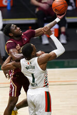Boston College guard Jay Heath, rear, shoots as Miami forward Anthony Walker (1) defends during the second half of an NCAA college basketball gam  Friday, March 5, 2021, in Coral Gables, Fla. (AP Photo/Wilfredo Lee)