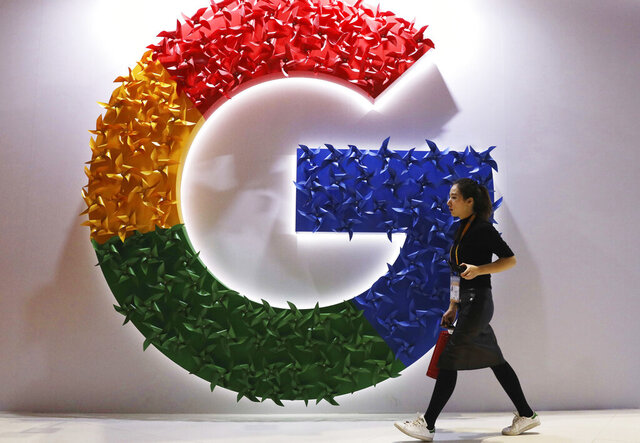 FILE - In this Monday, Nov. 5, 2018, file photo, a woman walks past the logo for Google at the China International Import Expo in Shanghai. Chinese tech giant Huawei is racing to develop replacements for Google apps. U.S. sanctions imposed on security grounds block Huawei from using YouTube and other popular Google