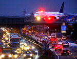 In this Tuesday, Nov. 7, 2017, file photo an Air Astana aircraft crosses a bridge over a highway at the international airport in Frankfurt, Germany. A German labor union is calling on security staff at Frankfurt airport to go on strike on Tuesday, Jan. 15, 2019 in a dispute over pay. (AP Photo/Michael Probst, file)