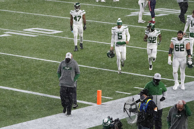 New York Jets head coach Adam Gase, left front, and players leave the field after losing an NFL football game to the New England Patriots, Sunday, Jan. 3, 2021, in Foxborough, Mass. (AP Photo/Charles Krupa)