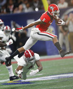Georgia wide receiver Terry Godwin (5) leaps over Alabama defensive back Saivion Smith (4) during the first half of the Southeastern Conference championship NCAA college football game, Saturday, Dec. 1, 2018, in Atlanta. (AP Photo/John Bazemore)