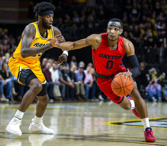 Dayton guard Rodney Chatman (0) drives around VCU forward Issac Vann (23) during the first half of an NCAA college basketball game, Tuesday, Feb. 18, 2020, in Richmond, Va. (AP Photo/Zach Gibson)