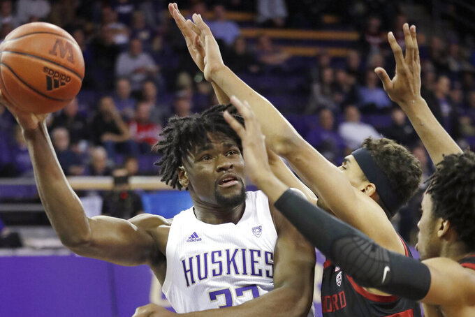 Washington's Isaiah Stewart looks for room to pass the ball during the first half of the team's NCAA college basketball game against Stanford on Thursday, Feb. 20, 2020, in Seattle. (AP Photo/Elaine Thompson)