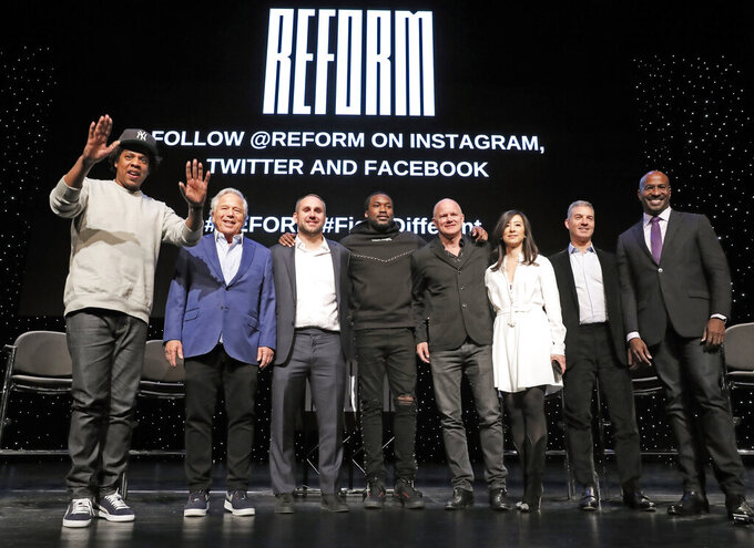"Entrepreneur ad recording artist Shawn ""Jay-Z"" Carter, from left, gestures as he poses with New England Patriots owner Robert Kraft, Philadelphia 76ers co-owner and Fanatics executive chairman Michael Rubin, recording artist Meek Mill, Galaxy Digital CEO and founder Michael Novogratz, Brooklyn Nets co-owner Clara Wu Tsai, Third Point CEO and founder Daniel S. Loeb, and REFORM Alliance CEO and political activist Van Jones after the group announced a partnership to transform the American criminal justice system, Wednesday, Jan. 23, 2019, in New York. (AP Photo/Kathy Willens)"