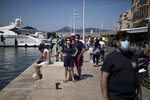 Tourists watch as a yacht docks at the Saint-Tropez port in southern France, Saturday Aug 8, 2020. The glamorous French Riviera resort of Saint-Tropez is requiring face masks outdoors starting Saturday, threatening to sober the mood in a place renowned for high-end, free-wheeling summer beach parties. (AP Photo/Daniel Cole)