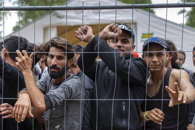 """FILE - In this file photo taken on Wednesday, Aug. 4, 2021, Migrants stand behind a fence inside the newly built refugee camp in the Rudninkai military training ground, some 38km (23,6 miles) south from Vilnius, Lithuania. Lithuanian authorities said Friday that the Baltic country has stemmed the flow of third country migrants illegally crossing from neighboring Belarus, saying the influx of people knocking at the external border of European Union seems to have halted and hundreds have been turned away. These people have a completely different culture. That's why we are worried about this,"""" said local resident Kristina Slovenska. """"We are worried about our safety."""" (AP Photo/Mindaugas Kulbis, File)"""