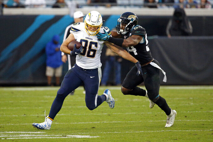 Los Angeles Chargers tight end Hunter Henry (86) tries to get away from Jacksonville Jaguars linebacker Donald Payne after a reception during the first half of an NFL football game, Sunday, Dec. 8, 2019, in Jacksonville, Fla. (AP Photo/Stephen B. Morton)