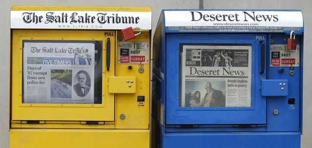 FILE - The Salt Lake Tribune and Deseret News newspaper boxes await customers on June 16, 2014, in Salt Lake City. The capital of Utah will go from two daily printed newspapers to none after both Salt Lake City's major publications moved to weekly print schedules in the last two days. The 170-year-old Deseret News said it will stop publishing daily starting next year in an announcement Tuesday, Oct. 27, 2020, a day after the Salt Lake Tribune made a similar announcement. The two publications' joint-operating agreement will also end at the end of the year. (AP Photo/Rick Bowmer, File)