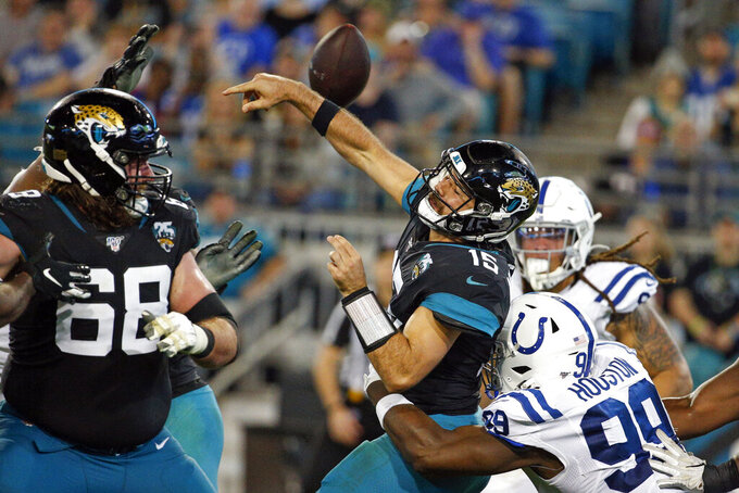 Jacksonville Jaguars quarterback Gardner Minshew II (15) fumbles the ball as he is hit by Indianapolis Colts defensive end Justin Houston (99)during the second half of an NFL football game, Sunday, Dec. 29, 2019, in Jacksonville, Fla. Jacksonville recovered the fumble for a first down. (AP Photo/Stephen B. Morton)