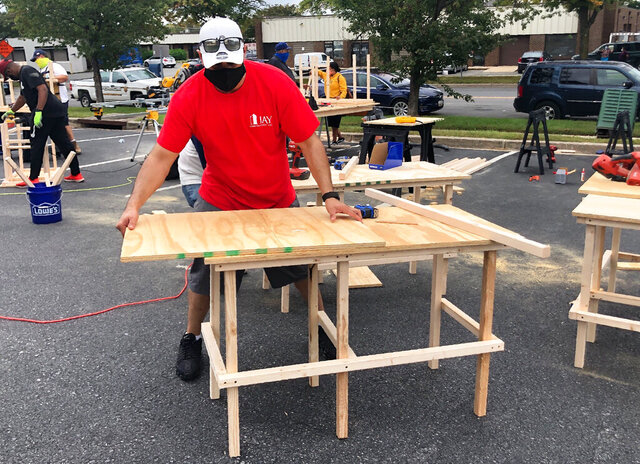 In this photo provided by Jessica Berrellez, her husband, Al Berrellez, builds a desk in Gaithersburg, Md., on Friday, Sept. 25, 2020. The couple, with the help of some 60 community volunteers, have built and donated over 100 desks so far to students and families in need. (Jessica Berrellez via AP)