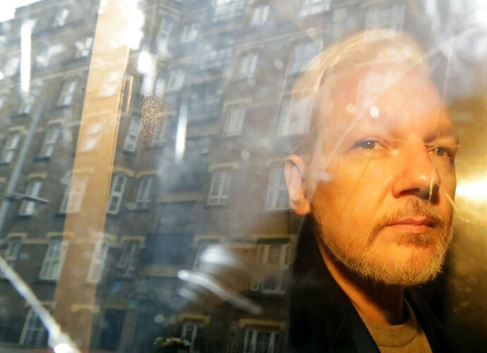 FILE - In this Wednesday May 1, 2019 file photo buildings are reflected in the window as WikiLeaks founder Julian Assange is taken from court, where he appeared on charges of jumping British bail seven years ago, in London. A lawyer for Julian Assange said Friday, Sept. 25, 2020 that the WikiLeaks founder's situation will be worse if President Donald Trump is re-elected in November than if Democrat rival Joe Biden wins. Edward Fitzgerald said at Assange's extradition hearing in London that Assange will suffer if he is sent to the U.S. to face spying charges regardless of who wins the Nov. 3 election. (AP Photo/Matt Dunham, File)