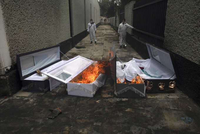 FILE - In this June 24, 2020 file photo, crematorium workers burn the coffins that contained the remains of people who died from the coronavirus after their cremation at the San Nicolas Tolentino cemetery in the Iztapalapa neighborhood of Mexico City. As Mexico approaches 200,000 in officially test-confirmed deaths from COVID-19, the real death toll is probably higher due to the country's extremely low rate of testing. (AP Photo/Marco Ugarte, File)