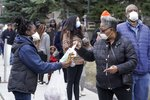 FILE - In this April 7, 2020, file photo, a worker hands out disinfectant wipes and pens as voters line up outside Riverside High School for Wisconsin's primary election in Milwaukee. Many Black voters are skeptical of voting by mail even as states seek to expand that option during the coronavirus pandemic. Decades of racism and voter disenfranchisement are at the heart of the uneasy choice facing Black voters. (AP Photo/Morry Gash, File)
