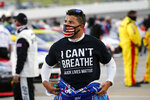 "FILE - In this June 10, 2020, file photo, driver Bubba Wallace, wearing an ""I Can't Breathe"" T-shirt waits for the start of a NASCAR Cup Series auto race in Martinsville, Va. A predominantly white sport with deep Southern roots and a longtime embrace of Confederate symbols, NASCAR was forced last summer to face its own checkered racial history during the country's social unrest. (AP Photo/Steve Helber, File)"