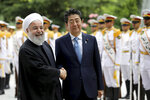 Japanese Prime Minister Shinzo Abe, center, shakes hands for the cameras with Iranian President Hassan Rouhani, during the official arrival ceremony, at the Saadabad Palace in Tehran, Iran, Wednesday, June 12, 2019. The Japanese leader is in Tehran on a mission to calm tensions between the U.S. and Iran. (AP Photo/Ebrahim Noroozi)