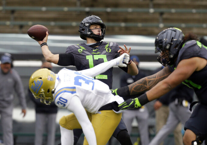 Oregon's Tyler Shough throws down field under pressure from UCLA's Elisha Guidry during the second quarter of an NCAA college football game Saturday, Nov. 21, 2020, in Eugene, Ore. (AP Photo/Chris Pietsch)
