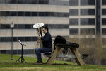 Joe LeFevre practices his tuba alone in a park Tuesday, March 24, 2020 on the first day of a stay-at-home order in Kansas City, Mo. Kansas City and surrounding counties instituted a 30-day mandatory stay-at-home order in an effort to stem the spread of the coronavirus. (AP Photo/Charlie Riedel)