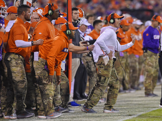 File-This Nov. 17, 2018, file photo shows, Clemson defensive coach Brent Venables being pulled back by an assistant during the first half of an NCAA college football game in Clemson, S.C. So as far as Venables is concerned, coaching defenses has always been challenging. Over 25 years in the business, the challenges have only increased as offenses have become more varied and multiple.  (AP Photo/Richard Shiro, File)