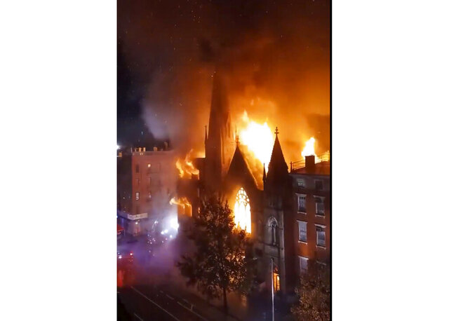Firefighters work to extinguish a fire that erupted from a building next to Middle Collegiate Church on Saturday, Dec. 5, 2020 in New York.  The historic 19th century church in lower Manhattan was gutted by a massive fire early Saturday that sent flames shooting through the roof. (Duke Todd via AP)