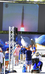 People watch lift-off during the Apollo 11 Launch Flashback, broadcast by CBS at the Kennedy Space Center's Apollo/Saturn V exhibit, Tuesday July 16, 2019. Guests viewed a rebroadcast of the 1969 launch from the grandstands at the Banana Creek viewing area to commemorate the launch of the Saturn V rocket and the Apollo 11 crew 50 years ago. (Joe Burbank/Orlando Sentinel via AP)
