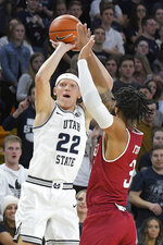 Utah State guard Brock Miller (22) takes a three point shot as Denver guard Jase Townsend (3) defends during the first half of an NCAA college basketball game Tuesday, Nov. 12, 2019, in Logan, Utah. (AP Photo/Eli Lucero)