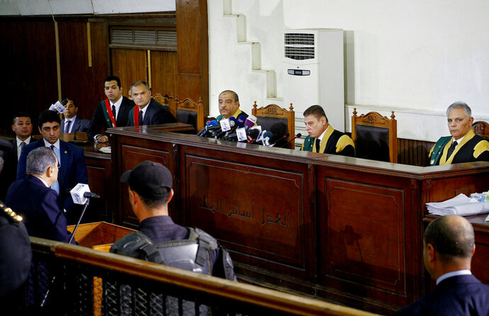 Former Egyptian President Hosni Mubarak, at left, testifies in a courtroom at the National Police Academy in Cairo, Egypt, Wednesday, Dec. 26, 2018. Two former Egyptian presidents appeared Wednesday in the same Cairo courtroom, with Mubarak testifying in a retrial of Mohammed Morsi on charges related to prison breaks at the height of the 2011 uprising that toppled Mubarak. (AP Photo/Ahmed Abdel Fattah)