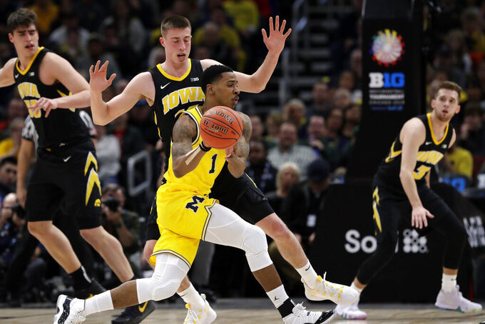 Michigan's Charles Matthews (1) drives past Iowa's Maishe Dailey during the first half of an NCAA college basketball game in the quarterfinals of the Big Ten Conference tournament, Friday, March 15, 2019, in Chicago. (AP Photo/Nam Y. Huh)