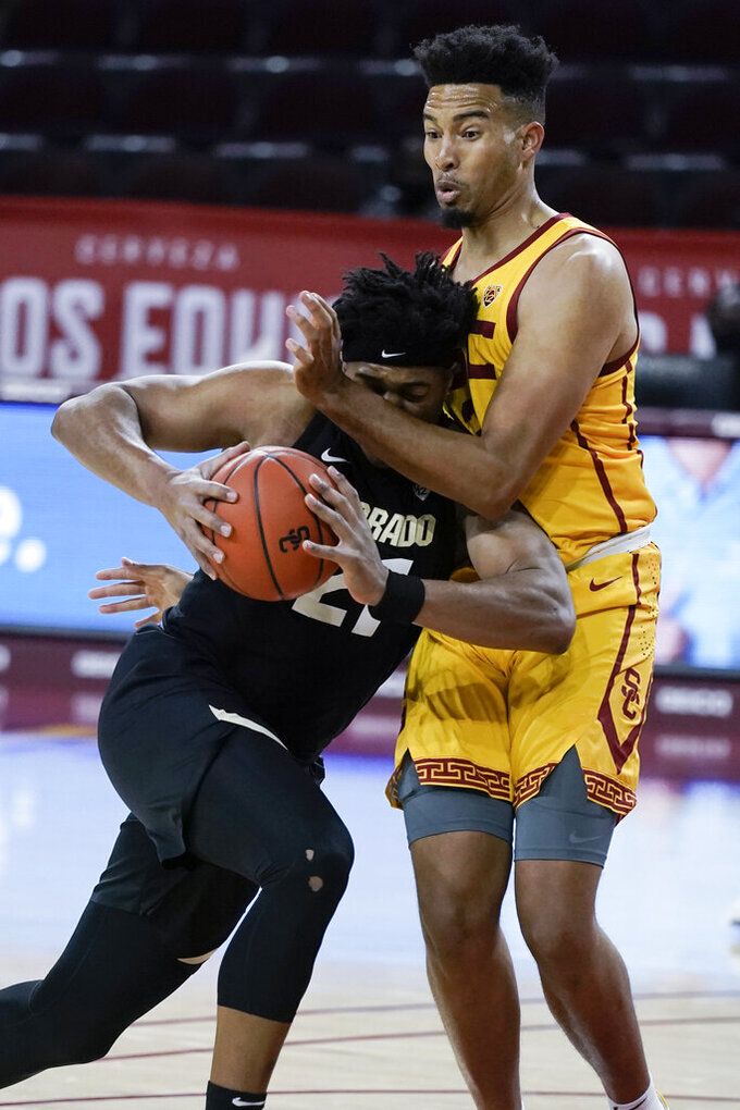 Colorado's Evan Battey, left, is defended closely by Southern California's Isaiah Mobley during the first half of an NCAA college basketball game Thursday, Dec. 31, 2020, in Los Angeles. (AP Photo/Jae C. Hong)