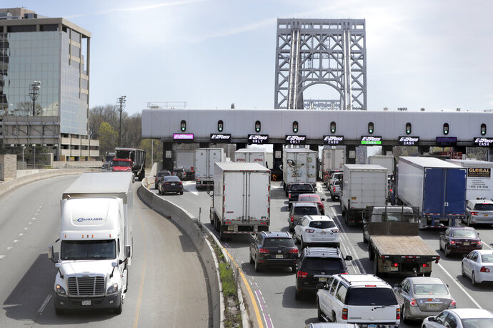 A truck, left, travels westbound off the George Washington Bridge as commuters line up to cross a toll plaza, Wednesday, April 17, 2019, in Fort Lee, N.J. U.S. Rep. Josh Gottheimer (NJ-5) and Rep. Bill Pascrell (NJ-9) held a news conference to announce they plan to fight back against New York City's proposed congestion tax on New Jersey commuters. The congressmen will propose legislation they say will ensure New Jersey motorists, who already pay up to $15 for bridge or tunnel tolls, won't be charged twice. New York's legislature approved a conceptual plan this month. that will allocate revenue to fix the city's mass transit system. New York would become the first American city to use so-called congestion pricing to reduce gridlock and fund mass transit improvements. (AP Photo/Julio Cortez)