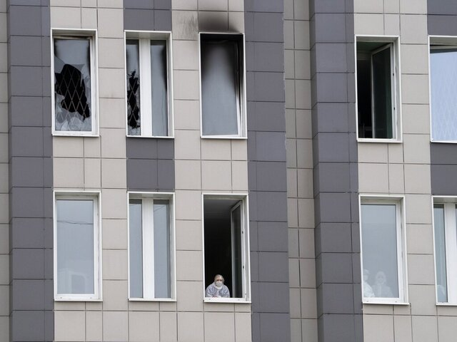 A member of the medical staff, bottom, looks through an open window next to the scene of a fire at St. George Hospital in St. Petersburg, Russia, Tuesday, May 12, 2020. A fire at St. George Hospital has killed five coronavirus patients. Russian emergency officials said all five had been put on ventilators. The emergency officials told the state Tass new agency the fire broke out in an intensive care unit and was put out within half an hour. (AP Photo/Dmitry Lovetsky)