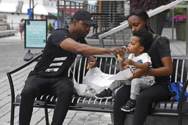 John Price and Bijan Black have lunch with their son Parker Price, 2, all of Seat Pleasant, Md., at the Wharf area in Washington, Friday, May 29, 2020. This was their first time venturing out since the coronavirus pandemic started. (AP Photo/Susan Walsh)