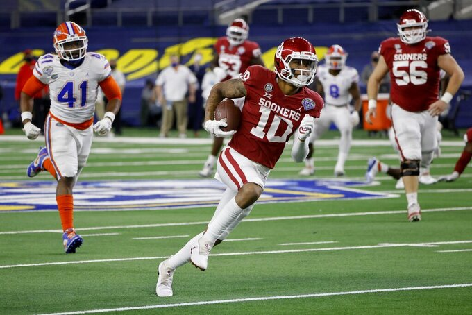 Oklahoma wide receiver Theo Wease (10) sprints to the end zone after a reception and scores a touchdown, ahead of Florida linebacker James Houston IV (41) during the first half of the Cotton Bowl NCAA college football game in Arlington, Texas, Wednesday, Dec. 30, 2020. (AP Photo/Michael Ainsworth)