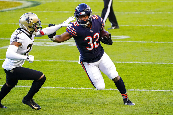 Chicago Bears running back David Montgomery (32) pushes off the tackle of New Orleans Saints cornerback Marshon Lattimore (23) in the first half of an NFL football game in Chicago, Sunday, Nov. 1, 2020. (AP Photo/Charles Rex Arbogast)