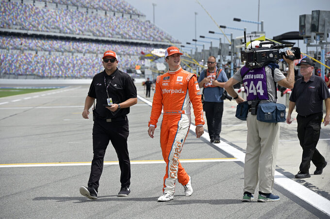 Driver Harrison Burton, second from left, walks to his vehicle on pit road before a NASCAR Xfinity Series auto race at Daytona International Speedway, Saturday, Aug. 28, 2021, in Daytona Beach, Fla. (AP Photo/Phelan M. Ebenhack)