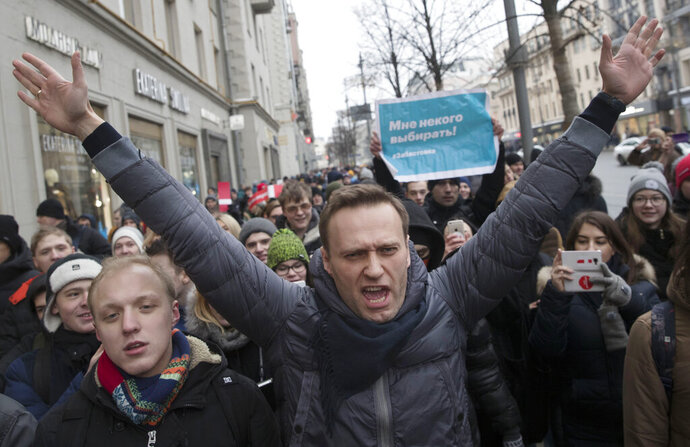 FILE - In this Jan. 28, 2018, file photo, Russian opposition leader Alexei Navalny, centre, attends a rally in Moscow, Russia. Navalny is an anti-corruption campaigner and the Kremlin's fiercest critic. He has outlasted many opposition figures and is undeterred by incessant attempts to stop his work. (AP Photo/Evgeny Feldman, File)