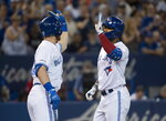 Toronto Blue Jays center fielder Teoscar Hernandez, right, celebrates his solo home run with Toronto Blue Jays right fielder Billy McKinney, left, while playing against the Texas Rangers during the sixth inning of a baseball game, Tuesday Aug. 13, 2019 in Toronto. (Nathan Denette/The Canadian Press via AP)