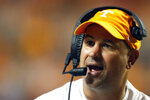 FILE - In this Oct. 5 2019, file photo, Tennessee head coach Jeremy Pruitt talks to a player in the second half of an NCAA college football game against Georgia in Knoxville, Tenn. The coronavirus is preventing prospects from leaving home to visit campuses and is keeping college coaches from traveling to evaluate players across the country. (AP Photo/Wade Payne, File)