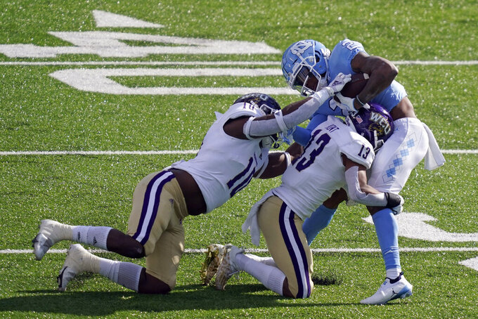 Western Carolina linebacker Willie Hampton (10) and cornerback Ronald Kent (13) tackle North Carolina wide receiver Dyami Brown (2) during the first half of an NCAA college football game in Chapel Hill, N.C., Saturday, Dec. 5, 2020. (AP Photo/Gerry Broome)