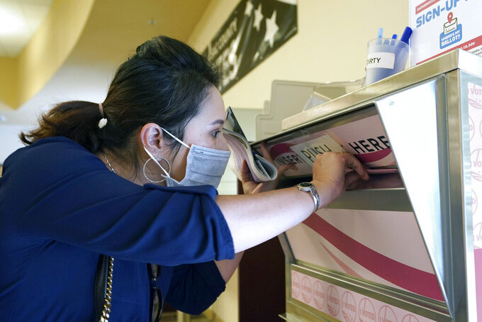 Amy Nguyen drops her recall ballot into the voting box at the Sacramento County Registrar of Voters office in Sacramento, Calif., Tuesday, Sept. 14, 2021. Tuesday is last day for California voters to cast their ballots in the recall election that could remove Gov. Gavin Newsom from office. (AP Photo/Rich Pedroncelli)