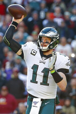 Philadelphia Eagles quarterback Carson Wentz (11) passes the ball in the first half of an NFL football game against the Washington Redskins, Sunday, Dec. 15, 2019, in Landover, Md. (AP Photo/Alex Brandon)