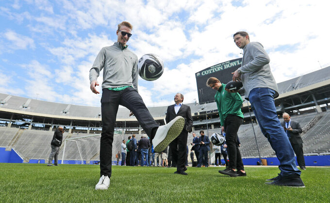 Dallas Stars' John Klingberg, left, plays with a soccer ball as Stars goaltender Ben Bishop, right, Miro Heiskanen, center right, and NHL commissioner Gary Bettman look on while touring the playing field of the Cotton Bowl in Dallas, Wednesday, March 20, 2019. The players and commissioner were on hand to announce the NHL Winter Classic hockey game between the Nashville Predators and the Dallas Stars to be played Jan. 1, 2020, at the Cotton Bowl in Dallas. (AP Photo/LM Otero)