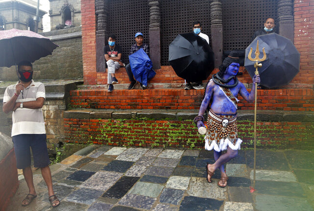 A member of a television crew stands dressed as Hindu god Shiva as Nepalese Hindu devotees wearing masks sit after offering prayers from outside the closed gate of Pashupatinath temple during the holy month of Shrawan in Kathmandu, Nepal, Monday, July 20, 2020. The temple has been remaining closed for almost four months as part of measures to control the spread of the coronavirus. (AP Photo/NIranjan Shrestha)