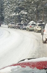 This photo provided by Chris Moats shows cars lined up along Alpine Meadows road in Alpine Meadows, Calif. on Friday, Jan. 17, 2020. One male skier died and another was seriously injured in an avalanche at Squaw Valley-Alpine Meadows, a ski resort in the Lake Tahoe. A search was ended, with officials saying they do not believe there were any more victims. (Chris Moats via AP)