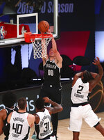 Brooklyn Nets forward Rodions Kurucs (00) dunks next to Los Angeles Clippers forward Kawhi Leonard (2) during the second half of an NBA basketball game Sunday, Aug. 9, 2020, in Lake Buena Vista, Fla. (Kim Klement/Pool Photo via AP)