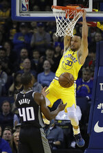 Golden State Warriors' Stephen Curry, right, scores over Sacramento Kings' Harrison Barnes (40) during the first half of an NBA basketball game Thursday, Feb. 21, 2019, in Oakland, Calif. (AP Photo/Ben Margot)
